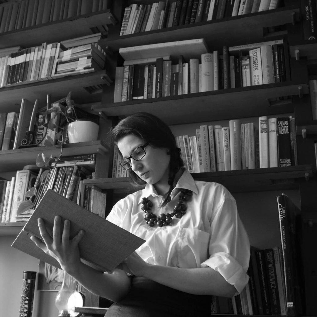 Młoda kobieta cztająca książkę na tle biblioteczki z książkami